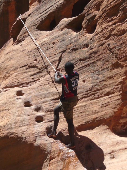 A man climbs up a steep red canyon wall with the aid of a rope and a stairway carved into the stone face.